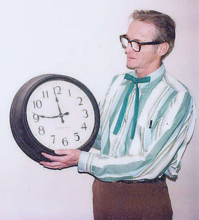Bill Lipscomb (William Lipscomb)           holding the clock with the bent minute hand